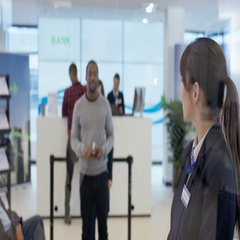 4K Worker in modern bank helps customer to use interactive atm machine Stock Footage