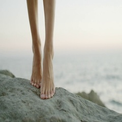 Female feet against the sea on the rock Stock Footage