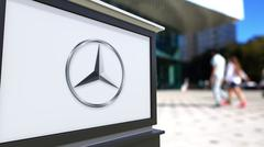 Street signage board with Mercedes-Benz logo. Blurred office center and walking Stock Illustration
