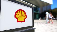 Street signage board with Shell Oil Company logo. Blurred office center and Piirros