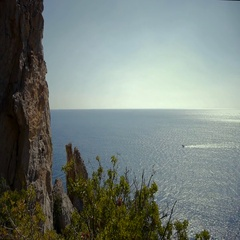 Boat floats on the sea against the backdrop of cliffs Stock Footage