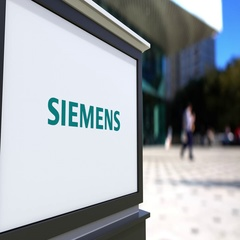 Street signage board with Siemens logo. Blurred office center and walking people Stock Footage