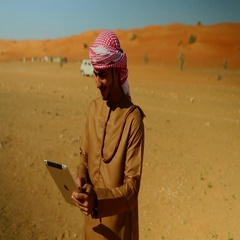 Arab man using digital tablet on desert, car in motion in the background. Stock Footage