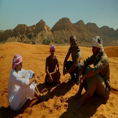 Arab men looking at quad biker on desert. Stock Footage