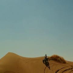 Arab man doing wheelie on quad bike at desert. Stock Footage