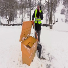 Janitor with phone and snow shovel at sandbox Stock Footage