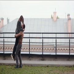 Man lifts his beloved in his arms and swirls around on a roof. Happy lovers have Stock Footage
