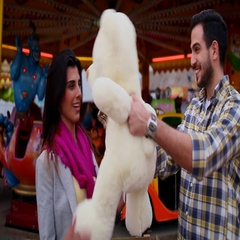 Man gifting teddy bear to woman at funfair, Dubai, United Arab Emirates. Stock Footage