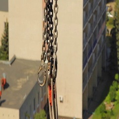 Tower crane swinging chains and hooks on city landscape background Stock Footage