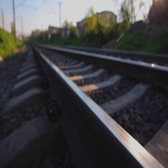 Metal railway track in suburbia on sunny spring day, close up Stock Footage