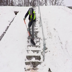 Janitor with snow shovel stepping down and cleaning stairs Stock Footage