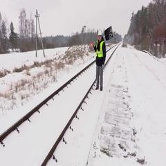 Railroad employee with  snow shovel walking near railway Stock Footage