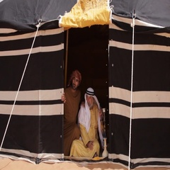 Father and son sitting inside a tent in the desert. Stock Footage