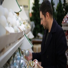 Man chooses Christmas decorations in a shop Stock Footage