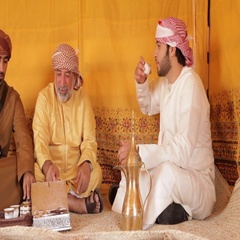 Arab men drinking gawa inside a tent. Stock Footage