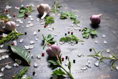 Garlic, red, black peppers, sea salt, greenery Stock Photos