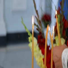 Hand lightens up a candle in church Stock Footage