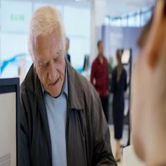 4K Worker at customer service desk assisting senior customer in modern bank Stock Footage