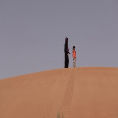 Mother and daughter walking down the desert dunes. Stock Footage