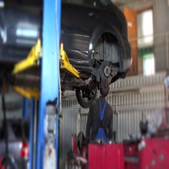 Car mechanic worker repair suspension of lifted automobile at repair garage Stock Footage