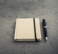 Notepad and pen lying on empty office table Stock Photos