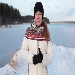 Caucasian woman in white down jacket and black hat and gloves on lakeshore Stock Footage