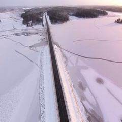 Aerial view of highway Kola, passing through forests and frozen river, Russia Stock Footage