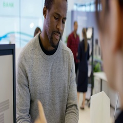 4K Worker at customer service desk assisting queue of customers in modern bank Stock Footage