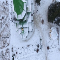 Camera flying above snowy green roof of wooden church Stock Footage