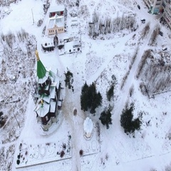 Camera flying over wooden church with green domes. Segezha, Russia Stock Footage