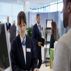 4K Portrait smiling bank worker assisting customer with a cash withdrawal Stock Footage