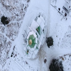 Camera rotating and lifting above snowy roof of wooden church and city. Russia Stock Footage