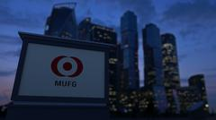 Street signage board with MUFG logo in the evening. Blurred business district Stock Illustration