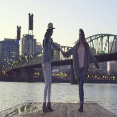 Young Women Practice Dance Moves At The End Of A Dock With City In Background Stock Footage