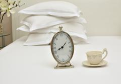 Alarm Clock and Cup on a Bed Kuvituskuvat
