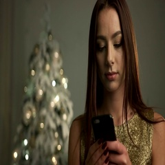 Cute smiling lady wearing gold dress, posing on a camera with smartphone on her Stock Footage