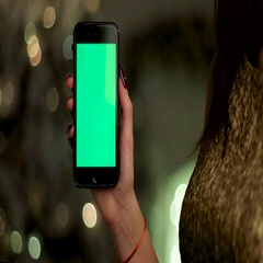 Close up of woman wearing gold dress, holding her mobile phone in hands. Green Stock Footage