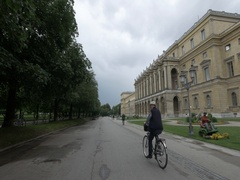 A man riding a bicycle in front of Residenz Munich Stock Footage
