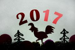 New Year's holiday symbol, shadow outline rooster and figures, frosty glass Stock Photos