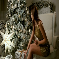 Attractive young woman wearing gold dress, sitting near Christmas tree and Stock Footage