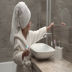 Girl in a towel and a bathrobe cleaning teeth Stock Footage