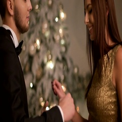 Happy young smiling couple having fun on a Christmas party and dancing near the Stock Footage