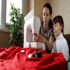 The child learns to sew on the sewing machine. Stock Footage