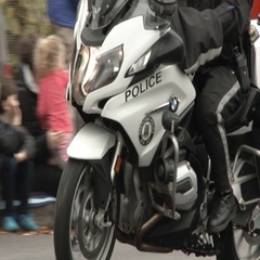 Police Motorcycle Driving Through Crowded Street Stock Footage