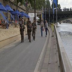 Security high alert - armed military soldiers patrol Paris urban beach Stock Footage
