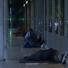 Homeless people prepare sleeping bags for night under facade Stock Footage
