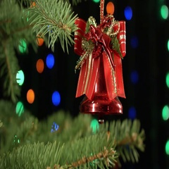 Christmas bell on the Christmas tree on dark background with garland Stock Footage