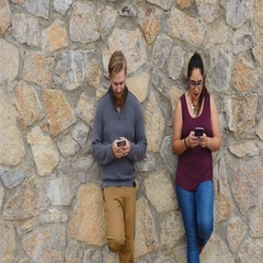 Young Millenial couple against rock wall laughing and texting Stock Footage