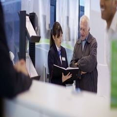 4K Bank worker at service desk assists couple with mortgage advice Stock Footage