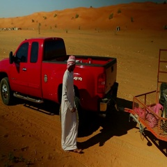 Arab man sitting on quad bike in pick up truck's carrier. Stock Footage